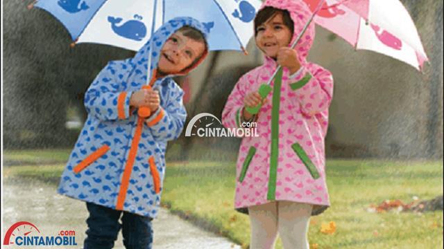 Gambar yang menunjukan dua orang anak yang sedang memakai payung dan jas hujan