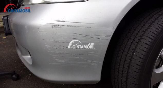 Gambar yang menunjukan mobil berwarna perak yang mengalami goresan