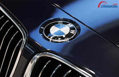 Gambar yang menunjukan kendaraan berwarna biru dengan logo BMW di depannya
