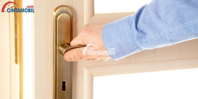 Gambar yang  menunjukan tangan yang sedang memegang gagang pintu rumah