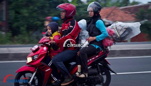 Gambar yang menunjukan pengendara motor yang mudik bersama keluarga