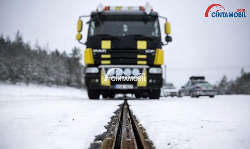 Gambar yang menunjukan rel listrik yang ada pada jalanan yang tertutup salju