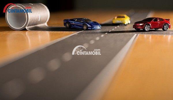 Gambar yang menunjukan mobil dengan pita jalan dengan dua mobil mainan