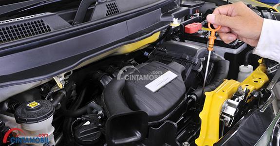 Gambar yang menunjukan teknisi yang sedang memeriksa bagian mesin mobil