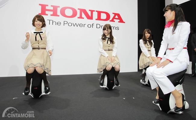 Gambar yang menunjukan beberapa wanita yang sedang mengendarai Honda UNI-CUB beta