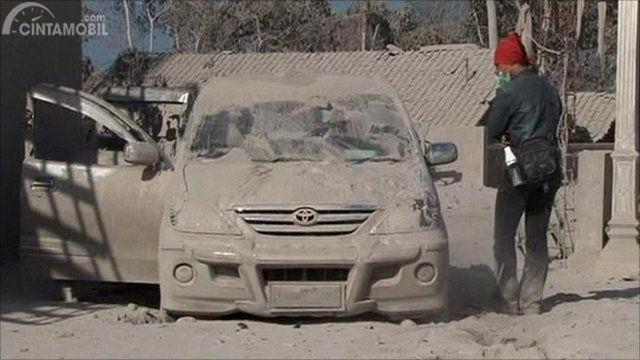 Gambar yang menunjukan kendaraan yang sedang ditutupi oleh debu vulkanik