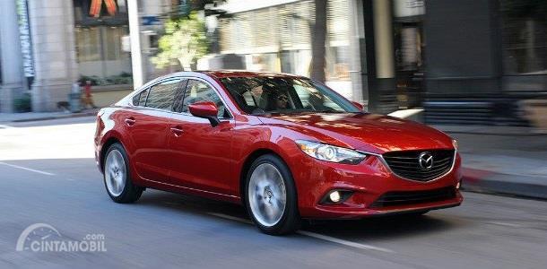 Gambar yang menunjukan mobil baru Mazda6 berwarna merah yang melaju di jalan