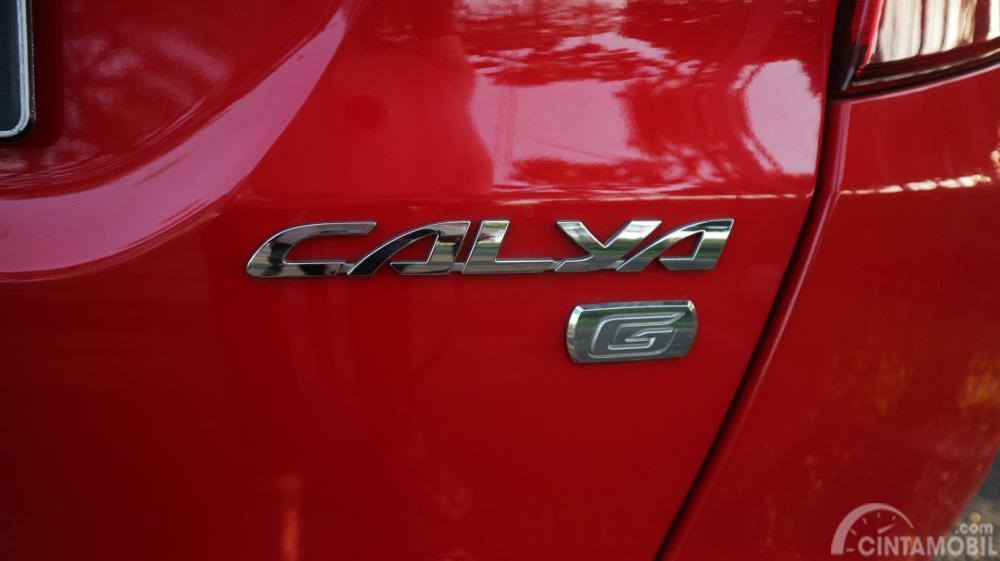Terlihat emblem krom Toyota Calya 1.2 G MT 2017 warna merah