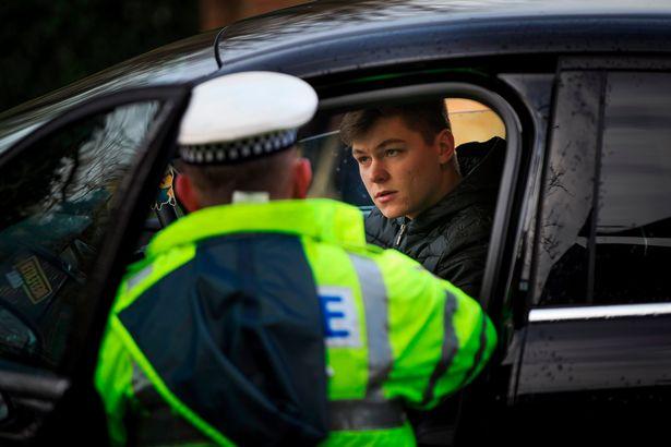 Gambar yang menunjukan polisi Inggris yang sedang menilang pengemudi mobil