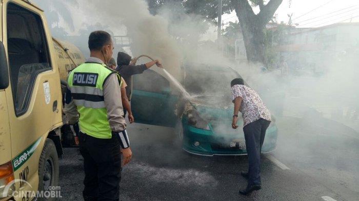 Gambar yang menunjukan polisi mencoba memadamkan mobil yang terbakar