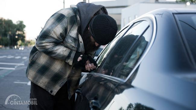 Gambar yang menunjukan seorang pencuri mobil yang sedang beraksi