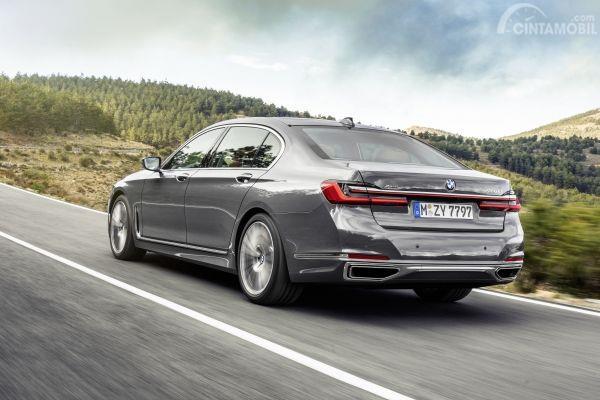 Buritan belakang BMW 7 Series 2019 berwarna abu-abu yang sedang berjalan di jalan naik turun