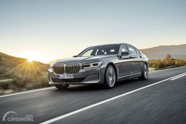 Tampilan BMW 7 Series 2019 berwarna abu-abu dilihat dari sisi depan yang sedang berjalan di jalan Indonesia
