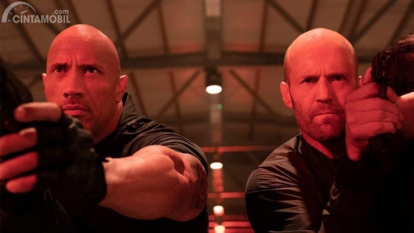 Dwayne Johnson dan Jason Statham memegang pistol