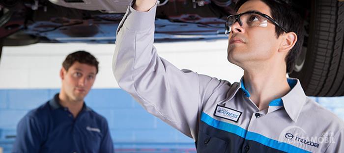 teknisi berkostum Mazda yang sedang melakukan perawatan pada mobil
