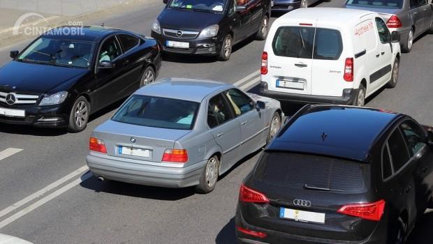 mobil berwarna biru mengekor mobil berwarna putih