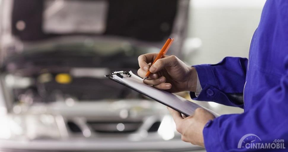 teknisi yang sedang mencatat perawatan berkala pada mobil
