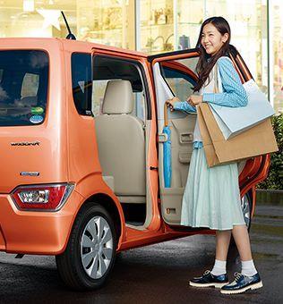 gambar menunjukan seorang wanita sedang membuka pintu mobilnya