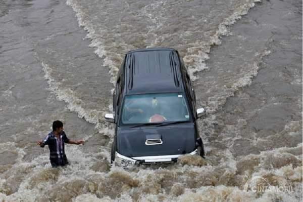 Toyota Fortuner warna hitam menerjang banjir dengan bantuan orang