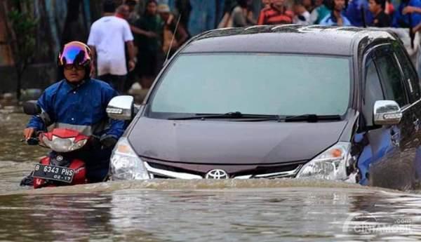 Toyota Avanza warna hitam sedang menerjang banjir dengan sebuah motor