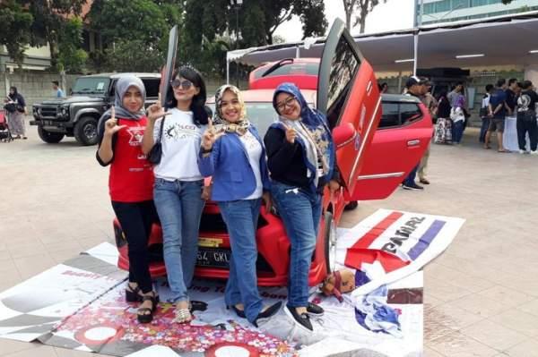 Anggota komunitas mobil wanita di depan mobil warna merah