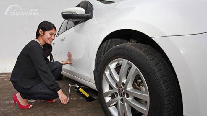 seorang wanita sedang melakukan proses ganti ban mobilnya