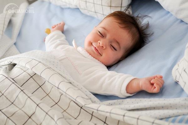 bayi berbaju putih yang sedang tertidur