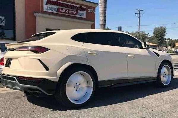 Lamborghini Urus warna krem difoto dari arah belakang