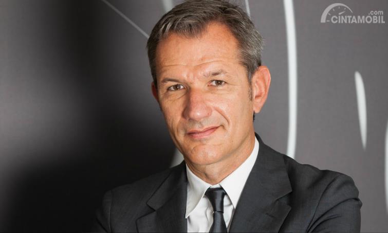 Bernard Loire memakai jas hitam dan kemeja putih