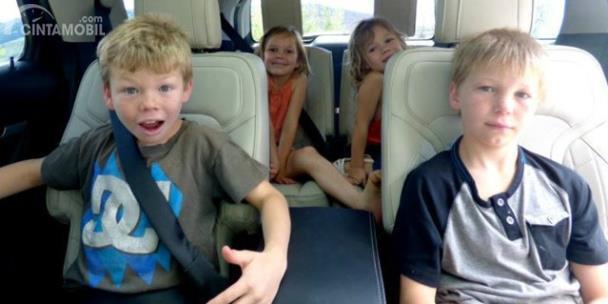 Anak kecil sedang duduk di kursi belakang mobil
