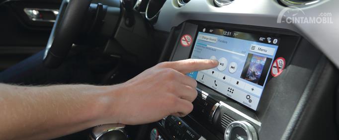 pengendara yang menekan layar sentuh ketika sedang menyetir