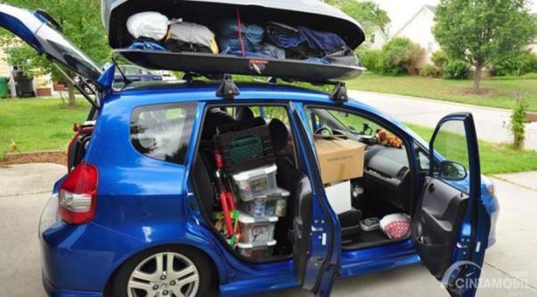 Honda Jazz warna biru dengan muatan penuh