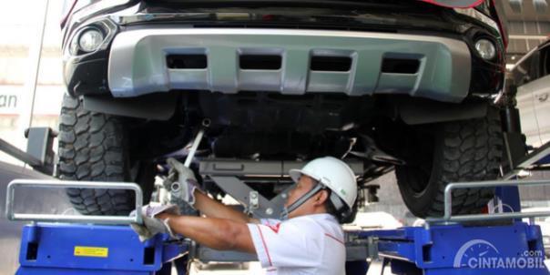 Teknisi memeriksa kaki-kaki mobil