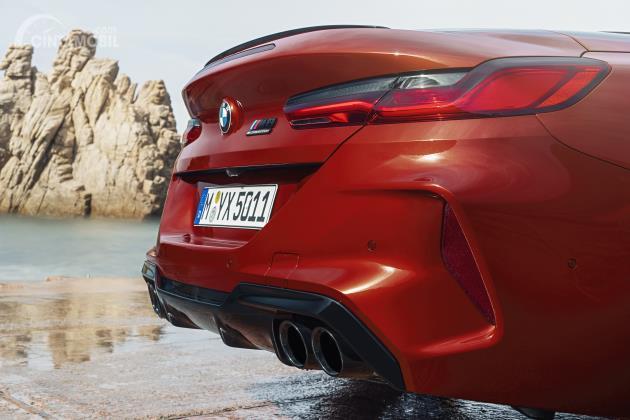 Gambar sebuah mobil BMW M8 Competition Cabriolet 2020 berwarna merah dilihat dari sisi belakang