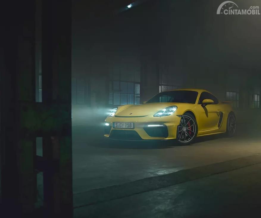 Foto sebuah mobil Porsche 718 Cayman GT4 2019 berwarna kuning dilihat dari sisi depan