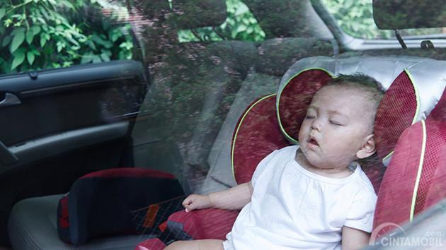 bayi berbaju putih yang sedang tertidur di dalam mobil
