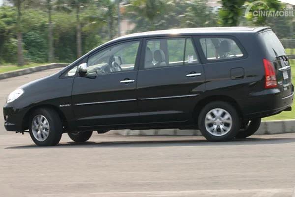 Gambar sebuah mobil Toyota Kijang Innova 2.7 V AT berwarna hitam sedang berbelok