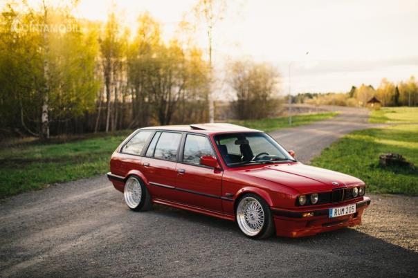 Gambar sebuah mobil BMW E30 Touring 2020 warna merah dilihat dari sisi depan