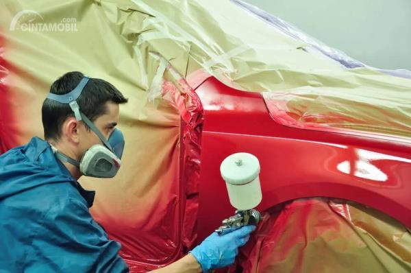 Seorang montir sedang melakukan proses pengecatan mobil