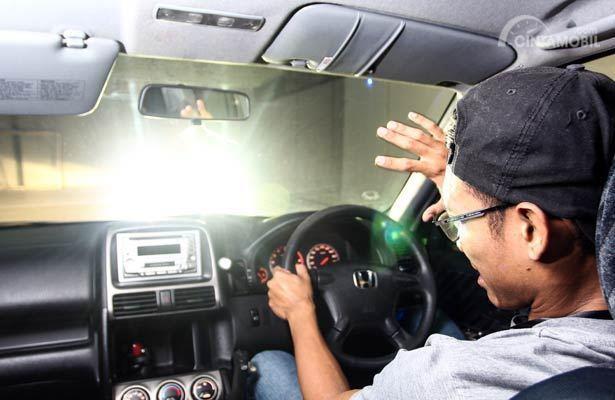 Foto menunjukkan seorang pengemudi merasa silau dengan lampu kendaraan lain
