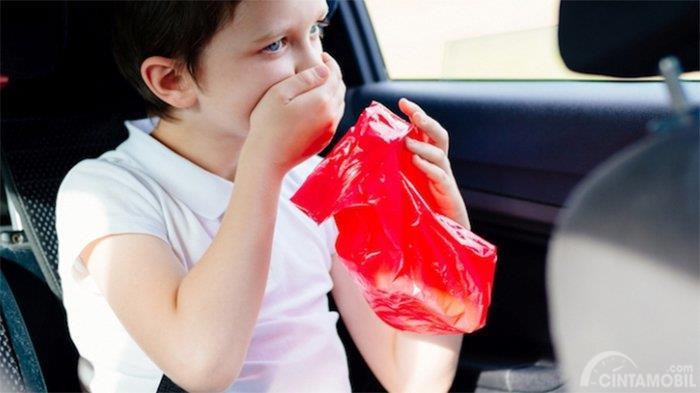 seorang anak berbaju putih yang sedang mabuk kendaraan