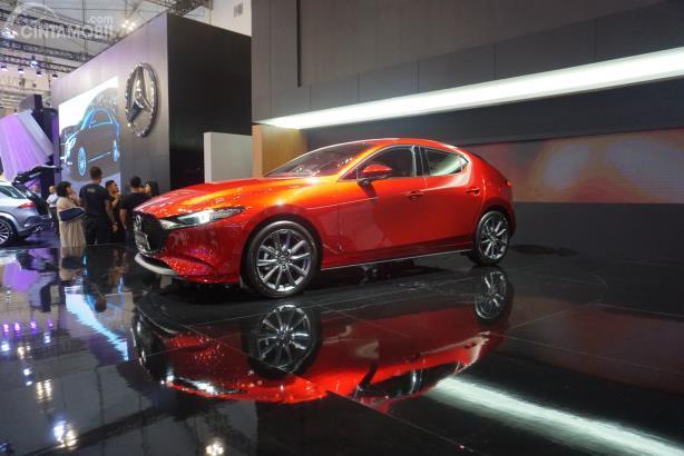 Gambar menunjukkan sebuah mobil Mazda 3 hatchback warna merah