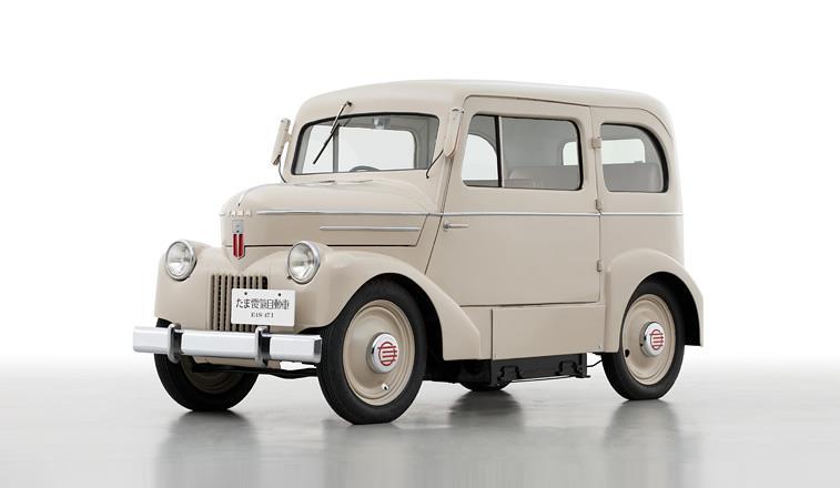 Gambar sebuah Mobil Nissan Tama Electric berwarna cream dilihat dari sisi depan