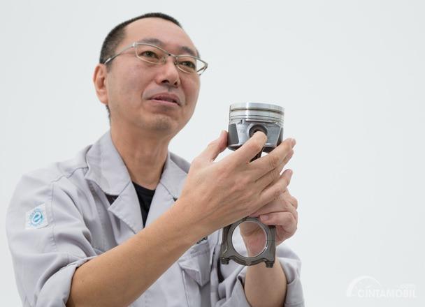 Yasunori Kanda sedang menjelaskan Piston mesin diesel Mazda