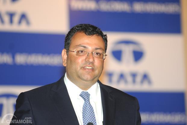 Pallonji Mistry di depan logo Tata Motors