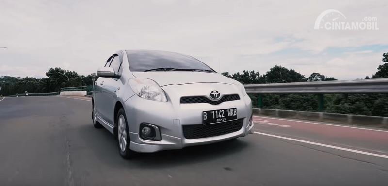 Gambar menunjukkan sebuah mobil Toyota Yaris E 2013 berwarna silver dilihat dari sisi depan