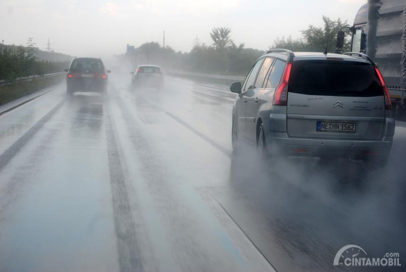 Gambar menunjukan mobil berjalan ketika turun hujan