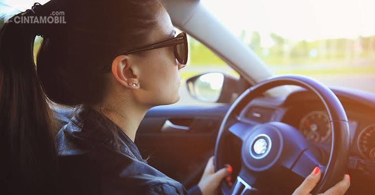 Gambar menujukan pengemudi wanita sedang Belajar mobil