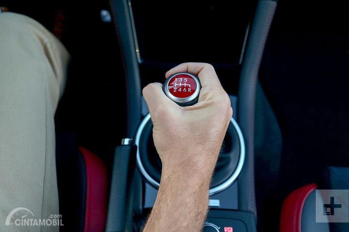 Seseorang mengendarai mobil manual