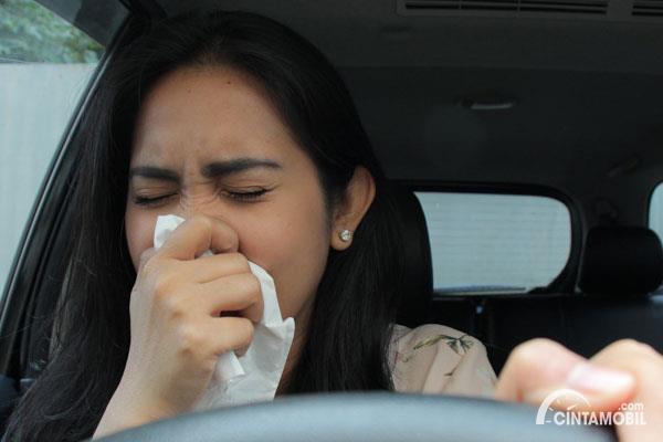Foto menunjukkan pengemudi wanita sedang terkena flu